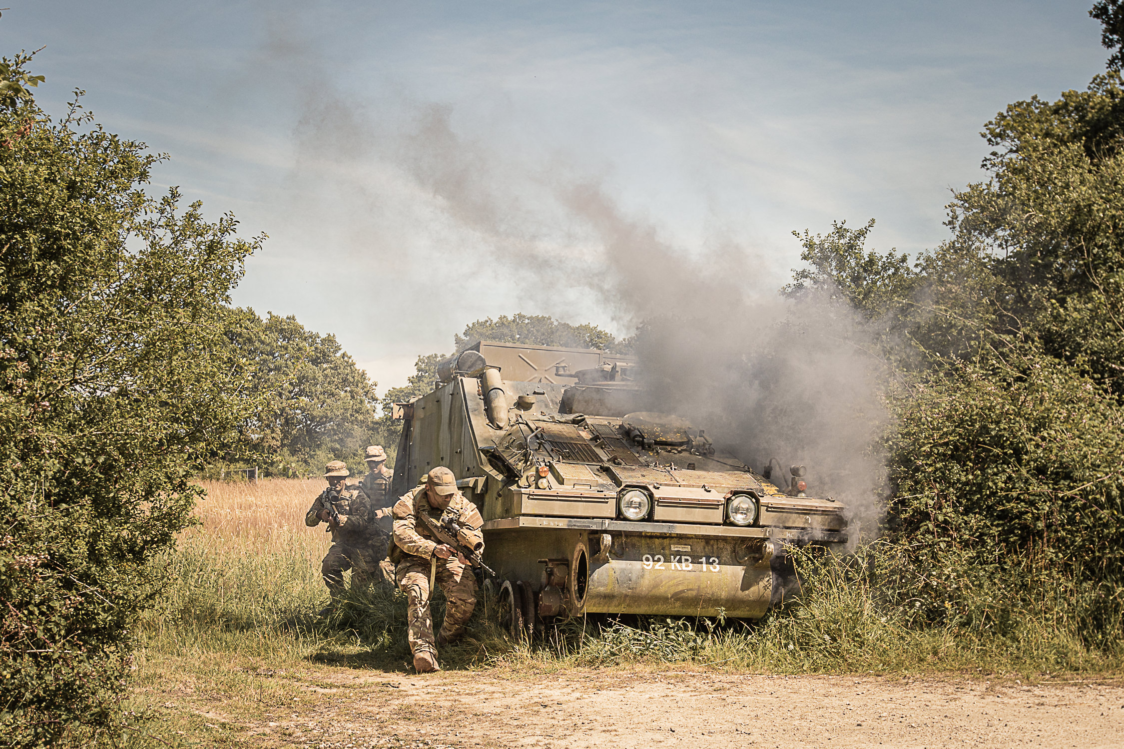 Uk Army soldiers criuched near a smoking military vehicle