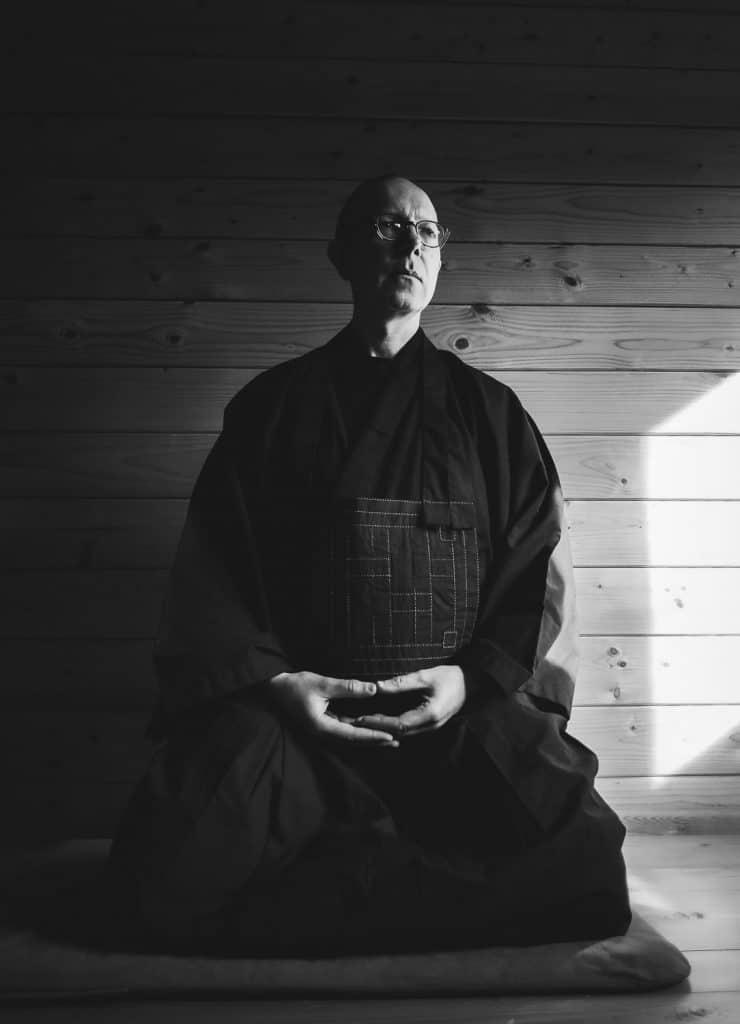 Black & white image of Kneeling man wearing budhist robes in meditation.